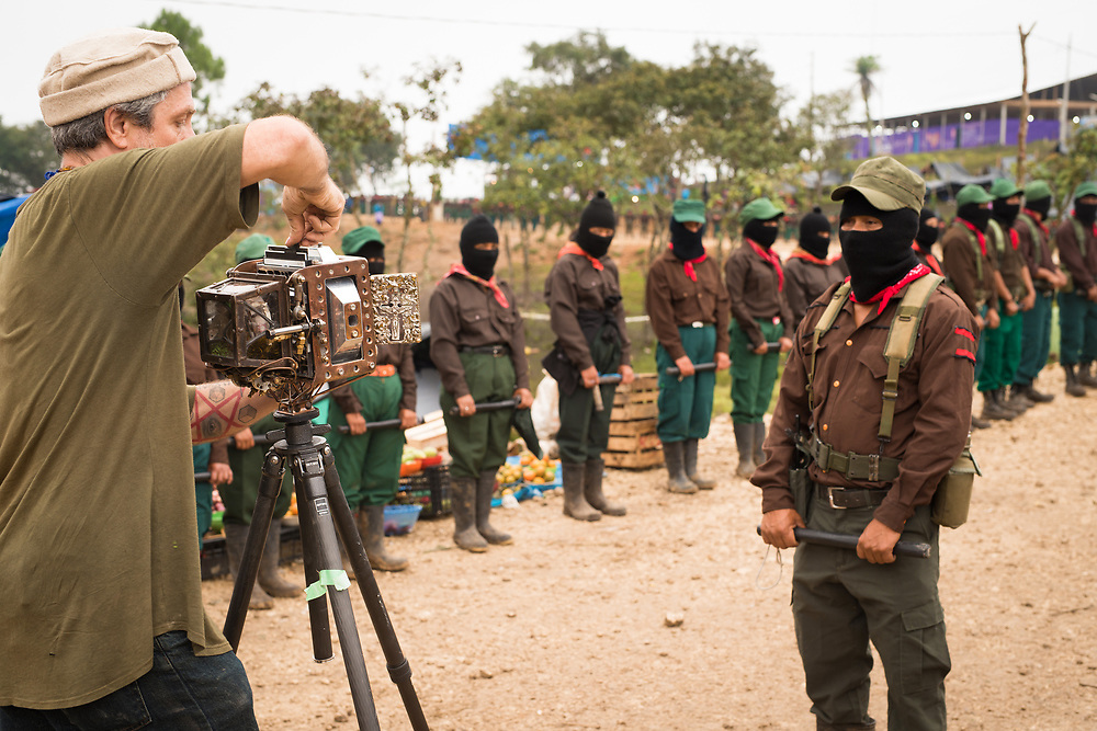 """""""Us & Them"""" photo shoot of a Zapatista commander and a couple hundred of his solders in a Zapatista Rebel encampment deep in the jungles of Palenque Mexico.<br /> <br /> Funny side note... <br /> Setting up shots, shooting and then tearing down takes a lot of time. During after this shot, the Zapatista convoy I was riding with left the Palenque compound and was on its way to another Rebel base about 6 hours away. <br /> Without me... <br />  I ran for the truck as it was leaving.  With 50lbs of gear on my back, I didn't make it...<br /> I watched the convoy disappear in the jungle with my gear bag leaving me with no money, no passport, no food, and a pathetic knowledge of the Spanish language... <br /> So I started hiking the road in the direction of the convoy surrounded by beautiful, thick jungle and the epic sounds of life coming from the jungle. <br /> Then after a few miles I came around a bend and there was the convoy, stopped! <br /> It's difficult keeping a convoy of 60+ vintage vehicles rolling smoothly on small, muddy Mexican jungle roads... <br /> I found my truck, climbed onboard and was greeted with cheers."""