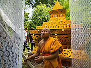 20 JUNE 2016 - DON KHONE, CHAMPASAK, LAOS: A Buddhist monk finishes the crematorium of a man from Don Khone village on Don Khone Island. Don Khone Island, one of the larger islands in the 4,000 Islands chain on the Mekong River in southern Laos. The island has become a backpacker hot spot, there are lots of guest houses and small restaurants on the north end of the island. In the southern Lao funeral tradition, the deceased is cremated at the place of his choosing, usually a place he (or she) was especially fond of. In this case, the man chose to be cremated in a small clearing in the jungle a few kilometers from his home.     PHOTO BY JACK KURTZ