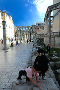 Two children (5 years old, 9 years old) playing in Peristyle, Diocletian Palace, Split, Croatia