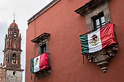 A Mexican flag flies over Corregidora Street with the steeple of San Francisco Church in San Miguel de Allende, Mexico.