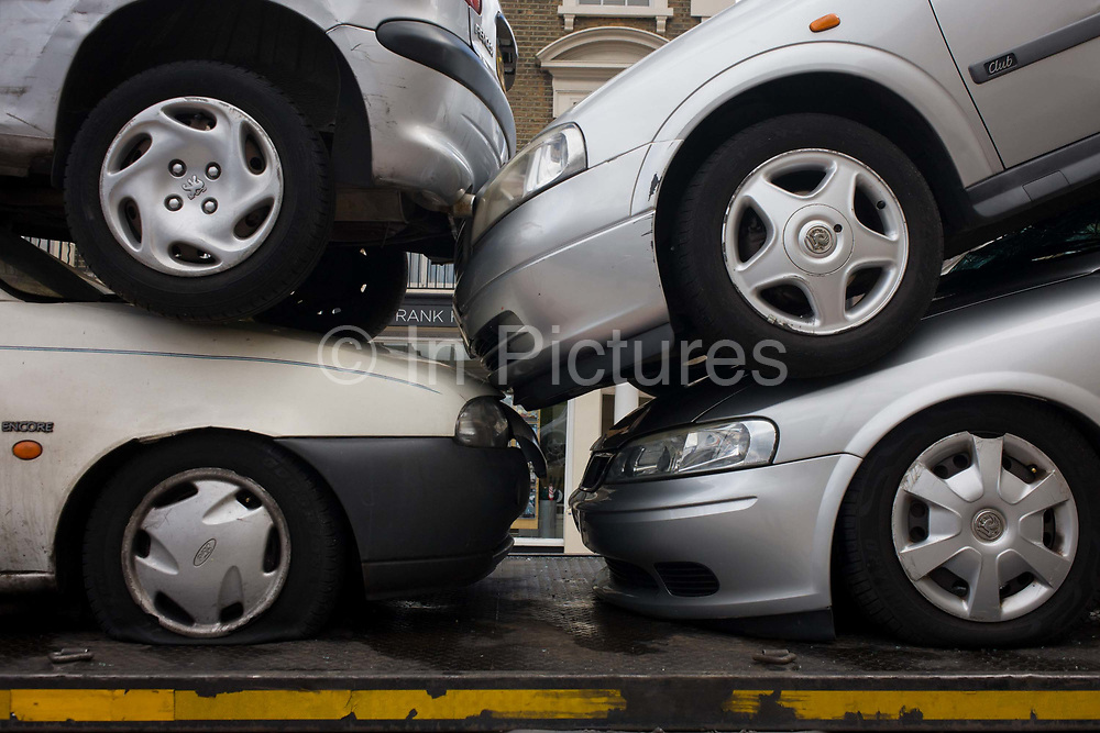 A stack of wrecked cars are transported through central London. We see the wheels and a flattened tyre of the squashed vehicles that may be taken away for scrap elsewhere. According to the Driver and Vehicle Licensing Agency (DVLA) there were 35 million vehicles licensed for use on the road in Great Britain in 2013. This is 1.5% up on 2012, the biggest annual increase since 2007.