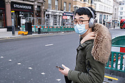 Young man wearing a face mask and headphones as the national coronavirus lockdown three continues on 29th January 2021 in London, United Kingdom. Following the surge in cases over the Winter including a new UK variant of Covid-19, this nationwide lockdown advises all citizens to follow the message to stay at home, protect the NHS and save lives.