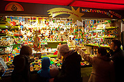 A family looks at a wooden toy stall, Weihnachtsmarkt am Kolner Dom / Cologne Cathedral  Christmas Market, Cologne.