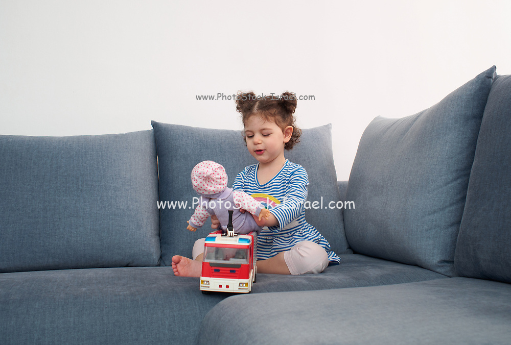 Toddler girl plays with her toys indoors