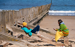 Portobello, Scotland, UK. 25 April 2020. Views of people outdoors on Saturday afternoon on the beach and promenade at Portobello, Edinburgh. Good weather has brought more people outdoors walking and cycling. Police are patrolling in vehicles but not stopping because most people seem to be observing social distancing. Women sitting chatting on wooden groyne.  Iain Masterton/Alamy Live News