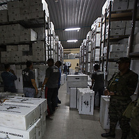 Cases of votes from across Honduras are stored in a warehouse in a government building in Tegucigalpa, workers select cases for a partial recount.