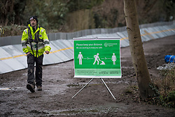 © Licensed to London News Pictures. 01/02/2021. Weybridge, UK. A member of the Environment Agency walks past flood defences installed along the river Thames at Weybridge in Surrey. Extra precautionis being taken because In 2014 Weybridge and the surrounding area was badly hit by flooding. Photo credit: Ben Cawthra/LNP