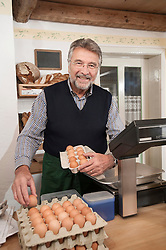 Portrait of a vendor arranging eggs in egg carton in the shop and smiling, Bavaria, Germany