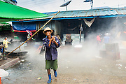 09 JUNE 2014 - YANGON, MYANMAR: A worker walks through a fog created by melting ice in the San Pya Fish Market (also spelled Sanpya). San Pya Fish Market in Yangon is one of the largest wholesale fish markets in Yangon. The market is busiest in early in the morning, from before dawn until about 10AM.    PHOTO BY JACK KURTZ
