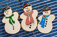 Closeup of three Christmas, sugar cookie snowmen arranged on a black mesh cooling rack over blue tablecloth.