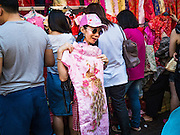 """31 JANUARY 2016 - BANGKOK, THAILAND: A woman shops for new clothes at a stand on Yaowarat Road, in Bangkok's Chinatown district, before the celebration of the Lunar New Year. Chinese New Year, also called Lunar New Year or Tet (in Vietnamese communities) starts Monday February 8. The coming year will be the """"Year of the Monkey."""" Thailand has the largest overseas Chinese population in the world; about 14 percent of Thais are of Chinese ancestry and some Chinese holidays, especially Chinese New Year, are widely celebrated in Thailand.           PHOTO BY JACK KURTZ"""