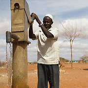 A community elder demonstrates a new pump-operated well in action. Wajir, North Eastern Kenya.