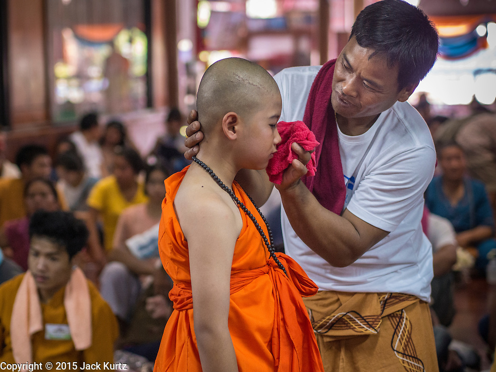 """06 APRIL 2015 - CHIANG MAI, CHIANG MAI, THAILAND: Family members help boys scrub off their make up during the ordination of the boys on the last day of the three day long Poi Song Long Festival in Chiang Mai. The boys spend the first two days of the ceremony dressed as royalty in ornate outfits before getting into the austere monks' robes. The Poi Sang Long Festival (also called Poy Sang Long) is an ordination ceremony for Tai (also and commonly called Shan, though they prefer Tai) boys in the Shan State of Myanmar (Burma) and in Shan communities in western Thailand. Most Tai boys go into the monastery as novice monks at some point between the ages of seven and fourteen. This year seven boys were ordained at the Poi Sang Long ceremony at Wat Pa Pao in Chiang Mai. Poy Song Long is Tai (Shan) for """"Festival of the Jewel (or Crystal) Sons.   PHOTO BY JACK KURTZ"""