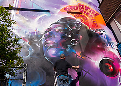 "© Licensed to London News Pictures; 02/04/2021; Bristol, UK. Artist Mr Cenz from London puts the finishing touches to ""United Souls United Goals"", a giant mural of Jen Reid, the woman who stood on the plinth of the statue of Edward Colston after it was torn down at a Black Lives Matter protest in Bristol in 2020 and of whom a statue was made and temporarily placed on the plinth. The mural is on the wall by The Canteen on Stokes Croft directly opposite Banksy's Mild Mild West mural, and replaces an earlier mural of Breakdancing Jesus. The mural is launched by The Bristol Eighteen and has the welcoming message ""Rise up Bristol, stand tall... Bristol's a city for all"" by poet Lawrence Hoo with Bristol's own street artist Inkie lending a hand to convey Lawrence Hoo's open-arms message of togetherness. The piece has been created to commemorate the Black Lives Matter protest in Bristol on June 7th 2020 and promote the ongoing global anti-racism movement. The Bristol Eighteen was formed, in the wake of the removal of Edward Colston's statue, to create a vehicle to raise funds for anti-racist educational organisations. Photo credit: Simon Chapman/LNP."