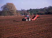 A913KF Tractor and trailer planting potato crop in field Suffolk sandlings England