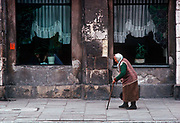 An elderly 1990s Polish lady struggles along a street and past a cafe whose walls are crumbling - the heritage of polluted communist decades, on 15th July 1990, in Krakow, Poland.