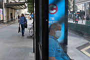 As some non-essential shops re-open, shoppers like this man waiting at a bus stop wearing face mask, return to Oxford Street while social distancing measures are put in place by the various retail shops which are open on 26th June 2020 in London, England, United Kingdom. As the July deadline approaces and government will relax its lockdown rules further, the West End remains quiet, apart from this popular shopping district, which itself has far fewer people on its pavements than normal.