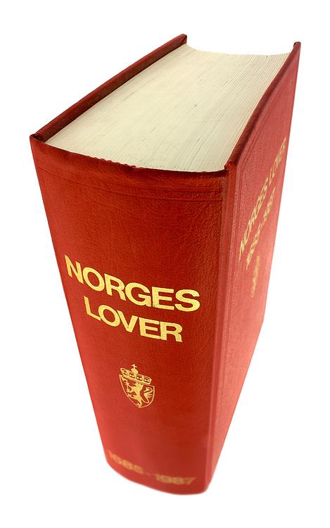 «Norges lover» på høykant sett skrått ovenfra, med hvit bakgrunn.