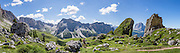 At Prera Longia/Pieralongia, between Alpe di Seceda and Alpe di Cisles/Cisles-Alm, walk by curious rock outcrops, near St. Christina, in Val Gardena, in South Tyrol, the Dolomites, Italy, Europe. In the background are the Puez Group (middle) and Langkofel Group (right, Sassolungo, 3181 meters/10,436 feet). The beautiful ski resort of Selva di Val Gardena (German: Wolkenstein in Gröden; Ladin: Sëlva Gherdëine) makes a great hiking base in the Trentino-Alto Adige/Südtirol (South Tyrol) region of Italy. For our favorite hike in the Dolomiti, start from Selva with the first morning bus to Ortisei, take the Seceda lift, admire great views up at the cross on the edge of Val di Funes (Villnöss), then walk 12 miles (2000 feet up, 5000 feet down) via the steep pass Furcela Forces De Sieles (Forcella Forces de Sielles) to beautiful Vallunga (trail #2 to 16), finishing where you started in Selva. The hike traverses the Geisler/Odle and Puez Groups from verdant pastures to alpine wonders, all preserved in a vast Nature Park: Parco Naturale Puez-Odle (German: Naturpark Puez-Geisler; Ladin: Parch Natural Pöz-Odles). UNESCO honored the Dolomites as a natural World Heritage Site in 2009. This panorama was stitched from 7 overlapping photos.