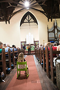 A young spectator gives herself the best view of Bernard Carney performing at St Matthews Church, Guildford, part of the 2019 Guildford Songfest