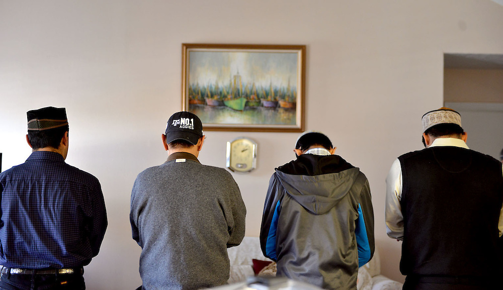 """From left Muslims Ahmad Kamal Rahman, Khalid Mahmood, Farhan Mahmood and Hassan Mahmood face East as they pray inside the home of Tasweer Rahman Friday, Jan. 16, 2015 in Bryan, Texas.  Rahman said that """"in the Muslim culture Friday is like Sunday to Christians as far as worship goes, we get together, we pray, we read scripture and we have a meal and tea afterwards.""""  (AP Photo/The Bryan-College Station Eagle, Sam Craft)"""
