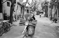Man carrying a load of new brushes on a bicycle in an old Beijing hutong