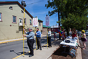 Counter-protesters at the Mifflinburg Pride Event hold poles with signs, cameras and a speaker.