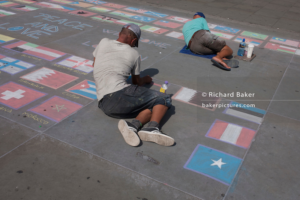 Street artists each draw the flags of other nations, on the pavement in Trafalgar Square, London UK.