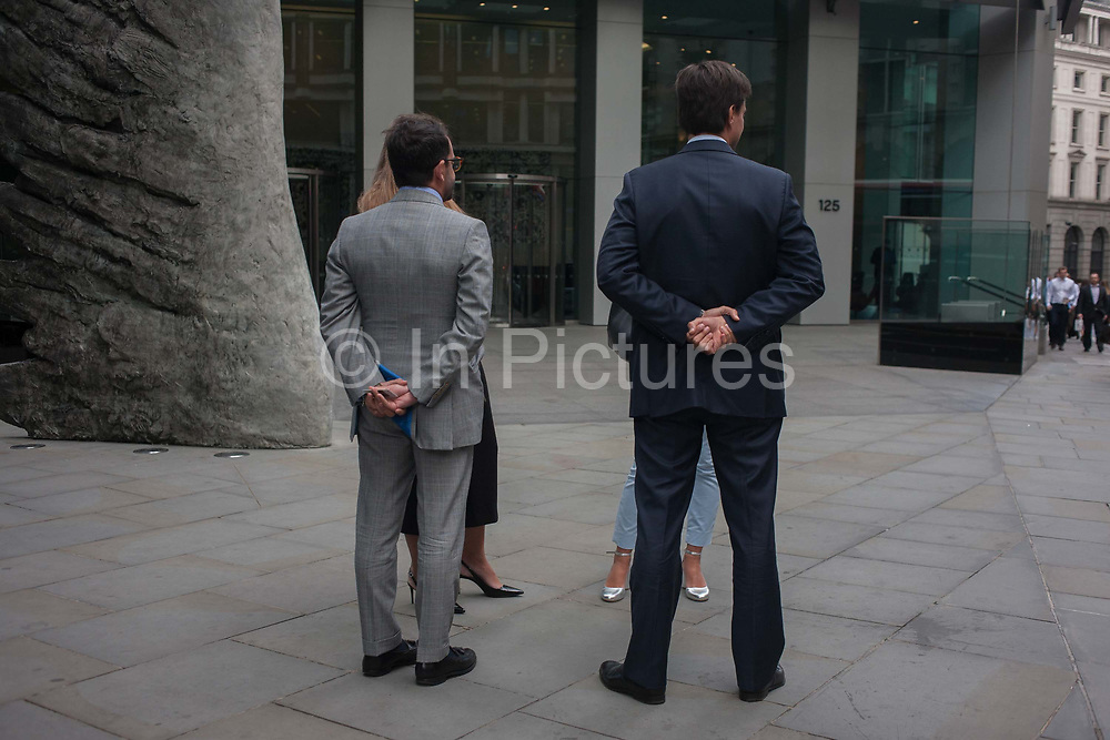 Two businessmen with female associates talk with hands behind their backs in the heart of the capitals financial district, founded by the Romans in the first century, on 8th September 2016, in the City of London, England UK.