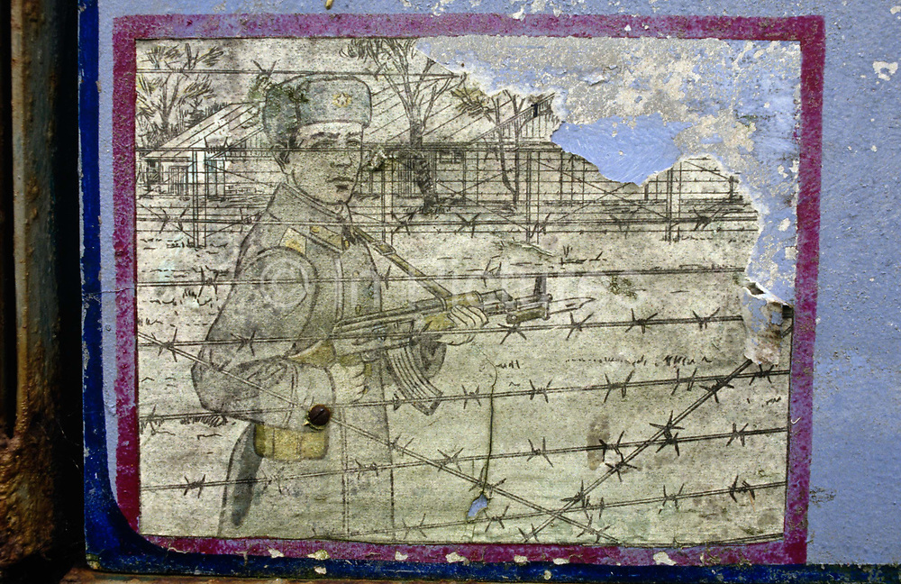 On the edge of an old Soviet parade ground, peeling murals show an instruction mural for guarding prison camps seen in this army boot camp in the former East German peninsular called Halbinsel Wustrow near Rostock. For the benefit of recruits or as reminders of Soviet discipline, the picture shows a soldier standing at the barbed wire of a generic Gulag holding his AK-47 weapon and dressed in fur hat and uniform from that era. Perhaps those training here were eventually to guard political prisoners though it is a reminder of a fallen ideology. Wustrow was once a WW2 German anti-aircraft artillery position then housed civilian refugees before the eventual Soviet occupation of the former DDR during the Cold War, up until 1990 and the fall of communism and the Berlin Wall. The camp was ransacked and all its assets stripped before its desertion that summer.