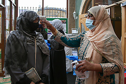 © Licensed to London News Pictures. 13/05/2021. London, UK. A muslim woman wearing face covering gets her temperature checked at London Islamic Cultural Society and Mosque, also known as Wightman Road Mosque in north London. Eid al-Fitr or the 'Festival of Breaking the Fast' celebrates the end of the month-long fast of Ramadan, and is being celebrated differently this year as a result of the coronavirus (COVID-19) pandemic. Prime Minister Boris Johnson announced that Covid-19 restrictions on social gatherings, meeting indoors and social contact will ease on May 17, meaning Eid celebrations this week still face restrictions.   Photo credit: Dinendra Haria/LNP
