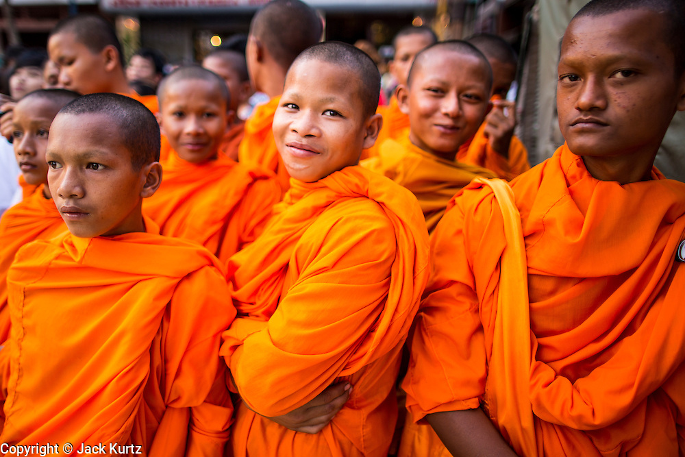 """03 FEBRUARY 2013 - PHNOM PENH, CAMBODIA:  Novice Buddhist monks watch the final Buddhist chanting service for former Cambodian King Norodom Sihanouk in the crematorium built for the King's funeral at the National Museum in Phnom Penh. Norodom Sihanouk (31 October 1922- 15 October 2012) was the King of Cambodia from 1941 to 1955 and again from 1993 to 2004. He was the effective ruler of Cambodia from 1953 to 1970. After his second abdication in 2004, he was given the honorific of """"The King-Father of Cambodia."""" He served as puppet head of state for the Khmer Rouge government in 1975-1976, before going into exile. Sihanouk's actual period of effective rule over Cambodia was from 9 November 1953, when Cambodia gained its independence from France, until 18 March 1970, when General Lon Nol and the National Assembly deposed him. Upon his final abdication in 2004, the Cambodian throne council appointed Norodom Sihamoni, one of Sihanouk's sons, as the new king. Sihanouk died in Beijing, China, where he was receiving medical care, on Oct. 15, 2012. His cremation will take place on Feb. 4, 2013. Over a million people are expected to attend the service.    PHOTO BY JACK KURTZ"""