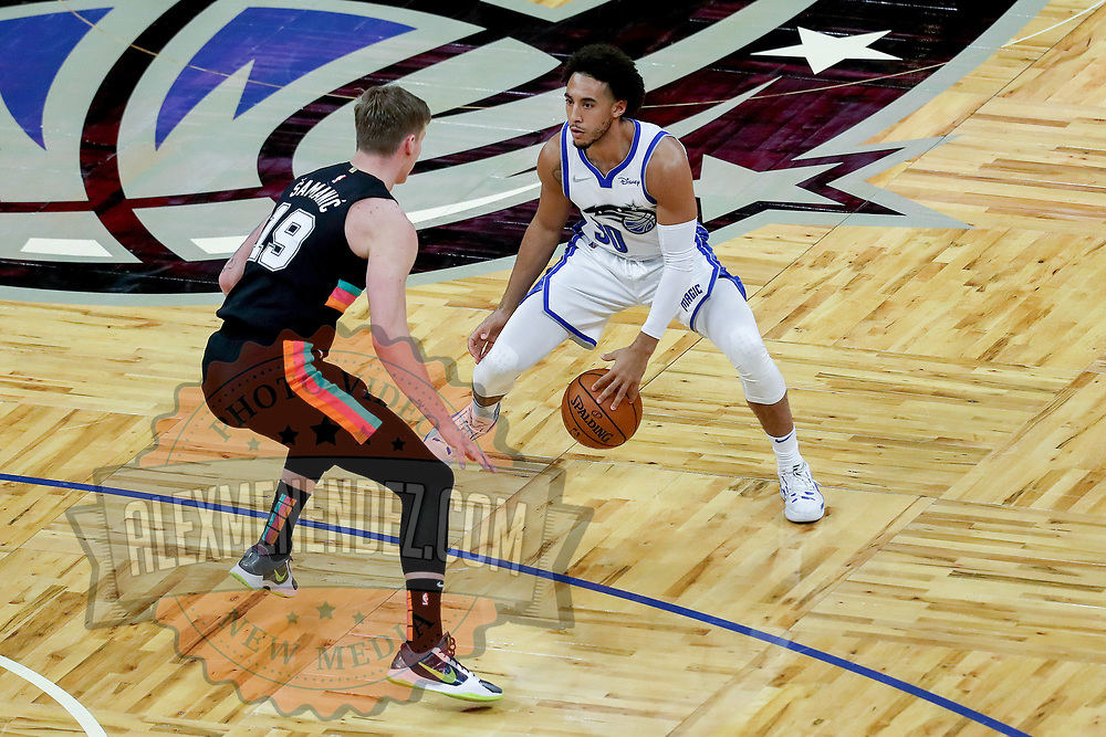 ORLANDO, FL - APRIL 12: Devin Cannady #30 of the Orlando Magic dribbles against Luka Samanic #19 of the San Antonio Spurs during the second half at Amway Center on April 12, 2021 in Orlando, Florida. NOTE TO USER: User expressly acknowledges and agrees that, by downloading and or using this photograph, User is consenting to the terms and conditions of the Getty Images License Agreement. (Photo by Alex Menendez/Getty Images)*** Local Caption *** Devin Cannady; Luka Samanic