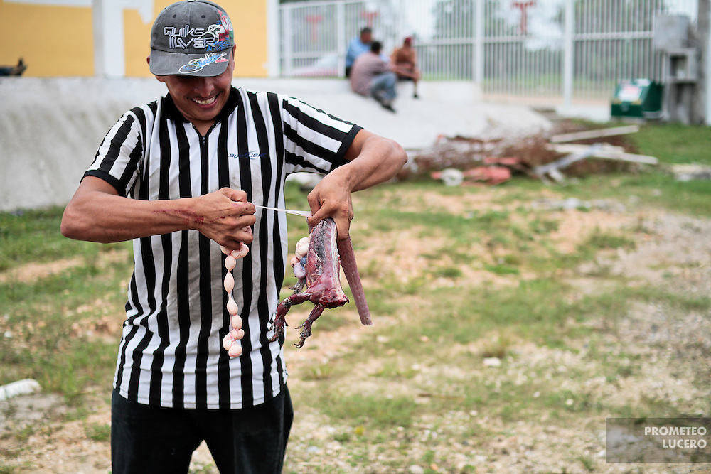 A central american migrant  spawns a garrobo (iguana) to be cooked after arriving to Tenosique, Tabasco. (Photo: Prometeo Lucero)