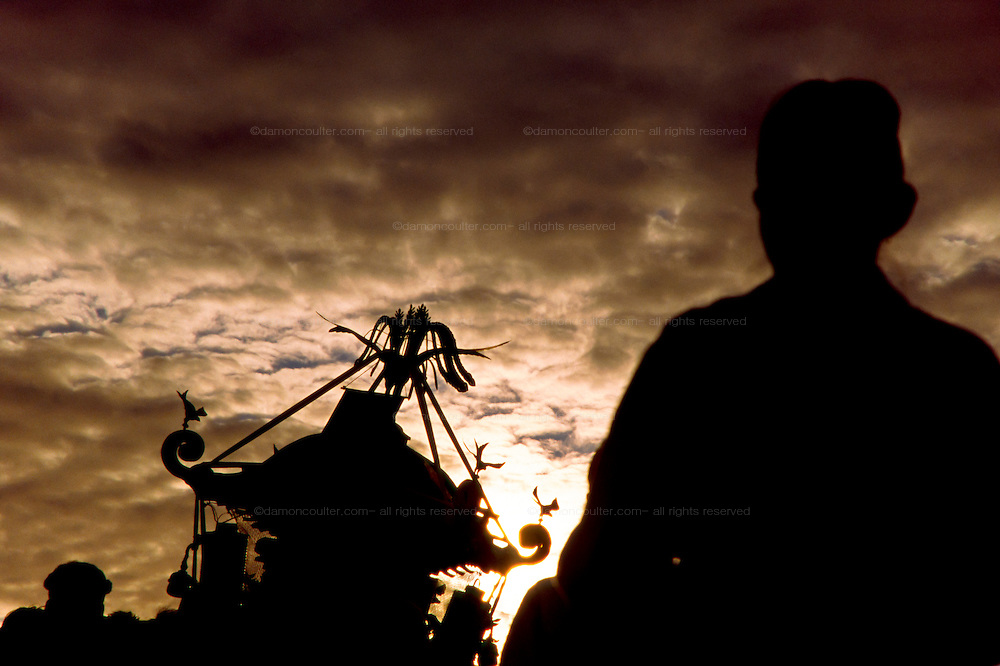 A mikoshi and supporter seen in silhouette during the Hamaorisai Matsuri that takes place on Southern Beach in Chigasaki near Tokyo, Kanagawa, Japan July 2006. The festivals marks the celebration of Marine Day in July. Over thirty Mikoshi or portable shrines are carried through the night from surrounding shrines to arrive on the beach for sunrise. They are then carried into the surf to purify them.