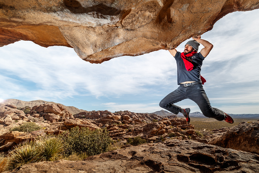 Jacob Garzaon hanging on lip of the Moonshine Roof, Hueco Tanks State Park & Historic Site, El Paso, Texas. USA.