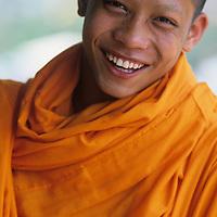 Asia, Laos, Luang Prabang, Portrait of Buddhist novice Thong Phat outside Wat Tham Phu Si temple