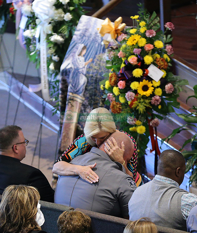 October 3, 2017 - Rockmart, GA, USA - October 3, 2017 Rockmart: A Polk County Police Department officer is consoled during the funeral of fellow Polk County police detective Kristen Hearne on Tuesday, Oct. 3, 2017, at the Victory Baptist Church in Rockmart, Ga. Hearne was killed while acting as a backup on what appeared to be a routine stolen car investigation when she was ambushed by a Walker County man with a long rap sheet and an outstanding warrant for his arrest. (Credit Image: © Curtis Compton/TNS via ZUMA Wire)