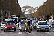 Traffic stops for pedestrians walking on zebra crossing on Champs-Élysées, Central Paris, France