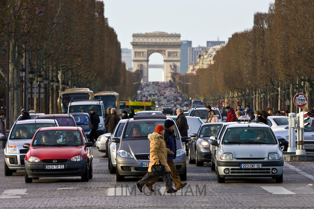 Traffic stops for pedestrians walking on zebra crossing on Champs-Élysées, Central Paris, France
