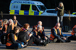 Insulate Britain climate activists sit in the clockwise carriageway of the M25 between Junctions 9 and 10 as part of a campaign intended to push the UK government to make significant legislative change to start lowering emissions on 21st September 2021 in Ockham, United Kingdom. The activists are demanding that the government immediately promises both to fully fund and ensure the insulation of all social housing in Britain by 2025 and to produce within four months a legally binding national plan to fully fund and ensure the full low-energy and low-carbon whole-house retrofit, with no externalised costs, of all homes in Britain by 2030.