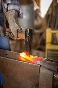 Hot metal being sculpted at Red Pig Tools.