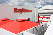 Model missiles at the Raytheon exhibition stand during the Farnborough airshow. Raytheon is a major American defence contractor and industrial corporation with core manufacturing concentrations in weapons and military and commercial electronics. It was previously involved in corporate and special-mission aircraft until early 2007. Raytheon is the world's largest producer of guided missiles. Established in 1922, the company reincorporated in 1928 and adopted its present name in 1959. The company has around 72,000 employees worldwide and annual revenues of approximately US$25 billion. More than 90% of Raytheon's revenues were obtained from military contracts and, as of 2007, it was the fifth-largest military contractor in the world and is the fourth largest defence contractor in the United States by revenue.