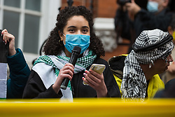 London, UK. 15th May, 2021. An activist wearing a keffiyeh addresses hundreds of people attending a Free Palestine SOS Colombia solidarity rally outside the Colombian embassy. Speakers at the event highlighted human rights abuses such as forced displacement being directed against Palestinians in Israel and the Occupied Territories and the killing, repression, detention and torture of peaceful demonstrators and human rights defenders in Colombia.