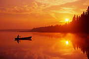 canoeing on Child's Lake at sunrise reflection<br /> Duck Mountain Provincial Park<br />Manitoba<br />Canada
