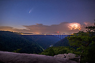 The comet NEOWISE hangs in the twilight above a distant simmering thunderstorm and the New River Gorge bridge spanning the canyon as viewed from the overlook at Long Point.