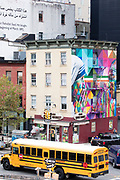 Street corner scene with yellow school bus, traffic lights, mural and Chelsea Square Market store at West 18th Street and Tenth Avenue in New York City, USA