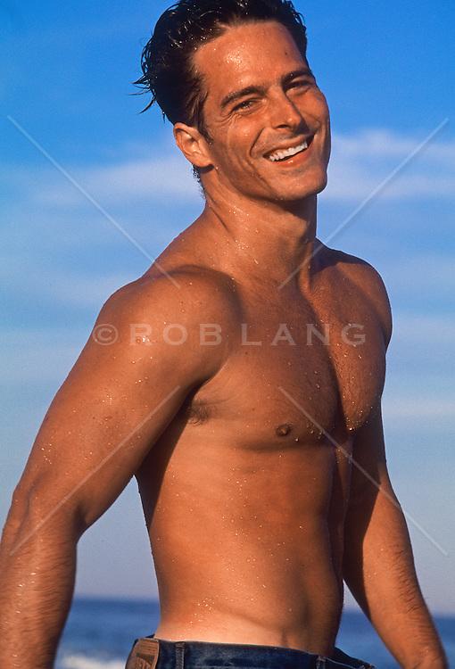 good looking man without a shirt enjoying himself at the beach