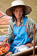 "10 JULY 2011 - DAMNOEN SADUAK, RATCHABURI, THAILAND:  A fried banana vendor in the floating market in Damnoen Saduak, Thailand. The Thai countryside south of Bangkok is crisscrossed with canals, some large enough to accommodate small commercial boats and small barges, some barely large enough for a small canoe. People who live near the canals use them for everything from domestic water to transportation and fishing. Some, like the canals in Amphawa and nearby Damnoensaduak (also spelled Damnoen Saduak) in Rajburi  province (also spelled Ratchaburi) are also relatively famous for their ""floating markets"" where vendors set up their canoes and boats as floating shops.  PHOTO BY JACK KURTZ"