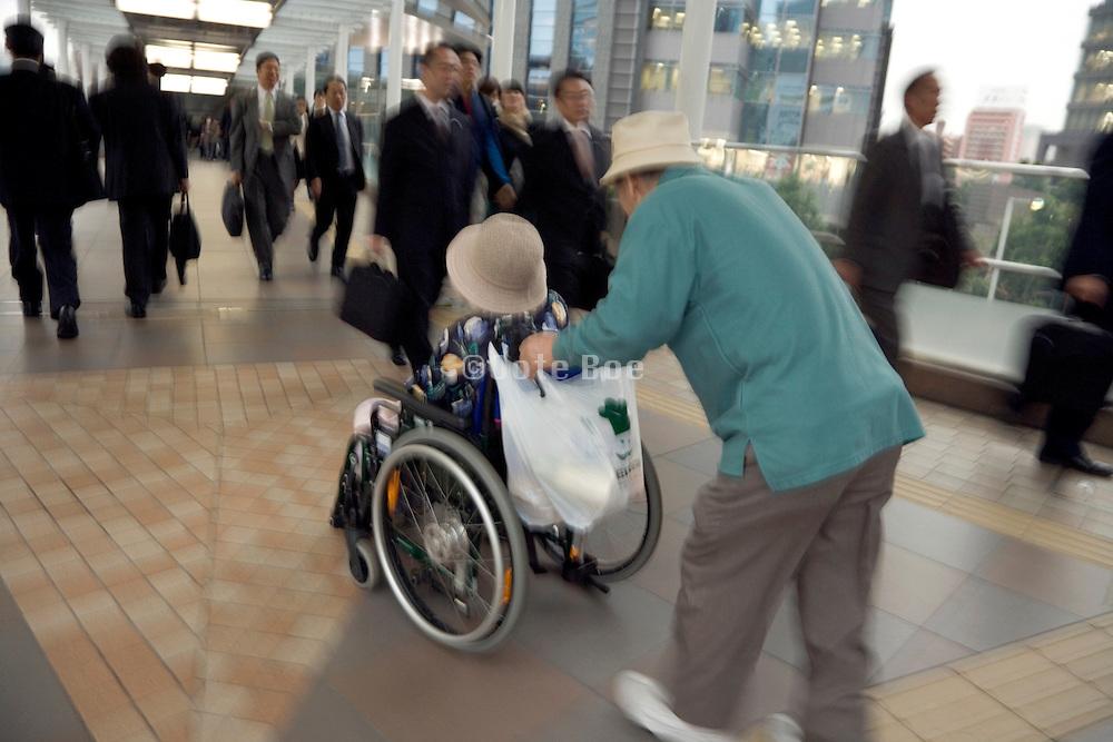 elderly couple going through a corridor where many businessmen are walking